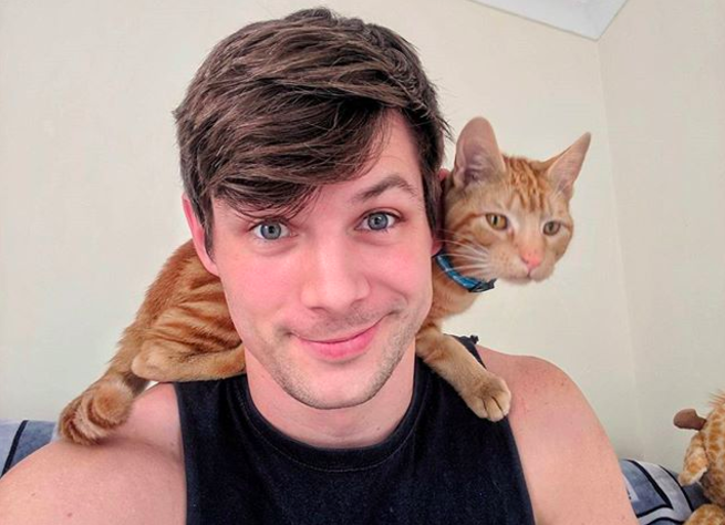 Photo of Oisín Tracey with a kitten on his shoulder.