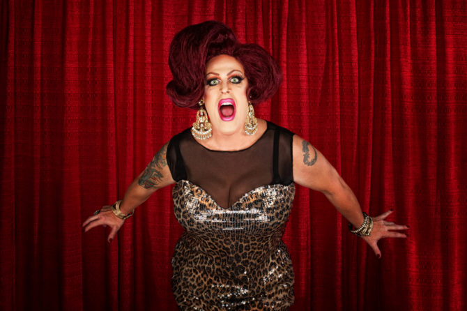 Drag queen standing in front of a red curtain