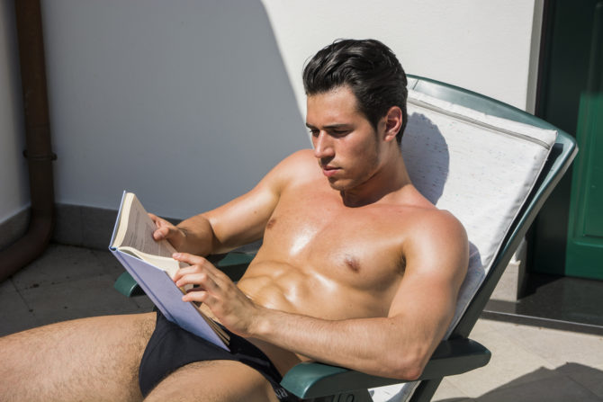 A hot guy reading a book wearing a speedo