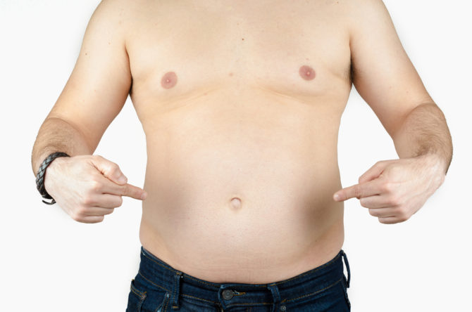 Shirtless man pointing to his belly.