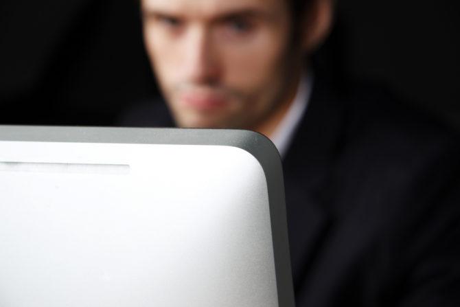 A man stares into a computer screen