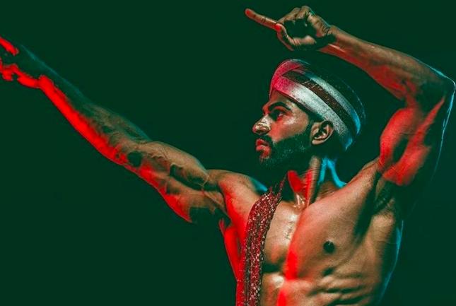 Shirtless Indian man showing off his biceps.