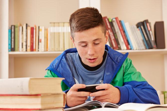 Teenage boy sending a text message