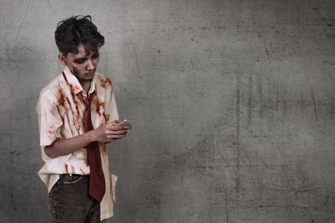 A zombie looking man holding a cellphone