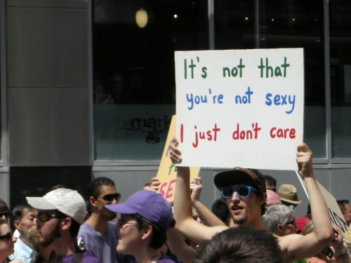 "Man holding a sign that reads: ""It's not that you're not sexy, it's just that I don't care"""