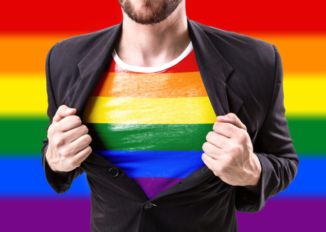 Man ripping open jacket to expose rainbow shirt