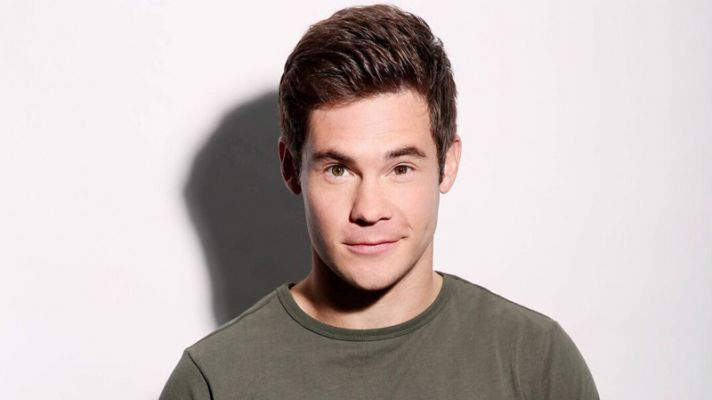 A headshot of actor Adam DeVine in a green sweater against a white wall.