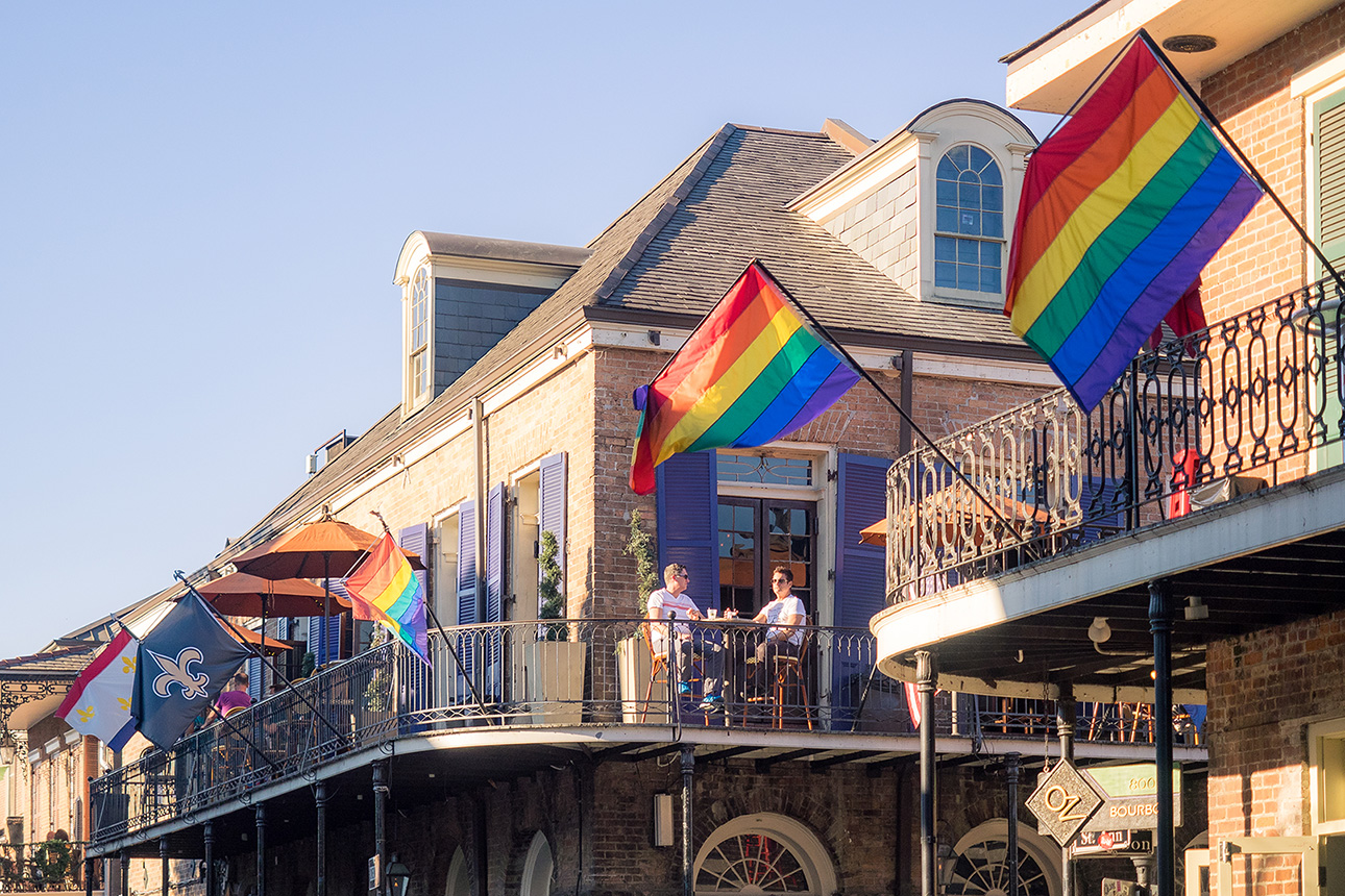 A photo of rainbow LGBTQ pride flags hanging on decks in the French Quarter of New Orleans.