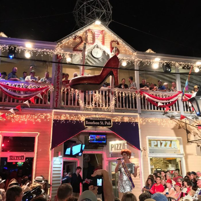 A drag queen hosting a New Year's Eve part in Key West, with a big red shoe in front of the word 2016.