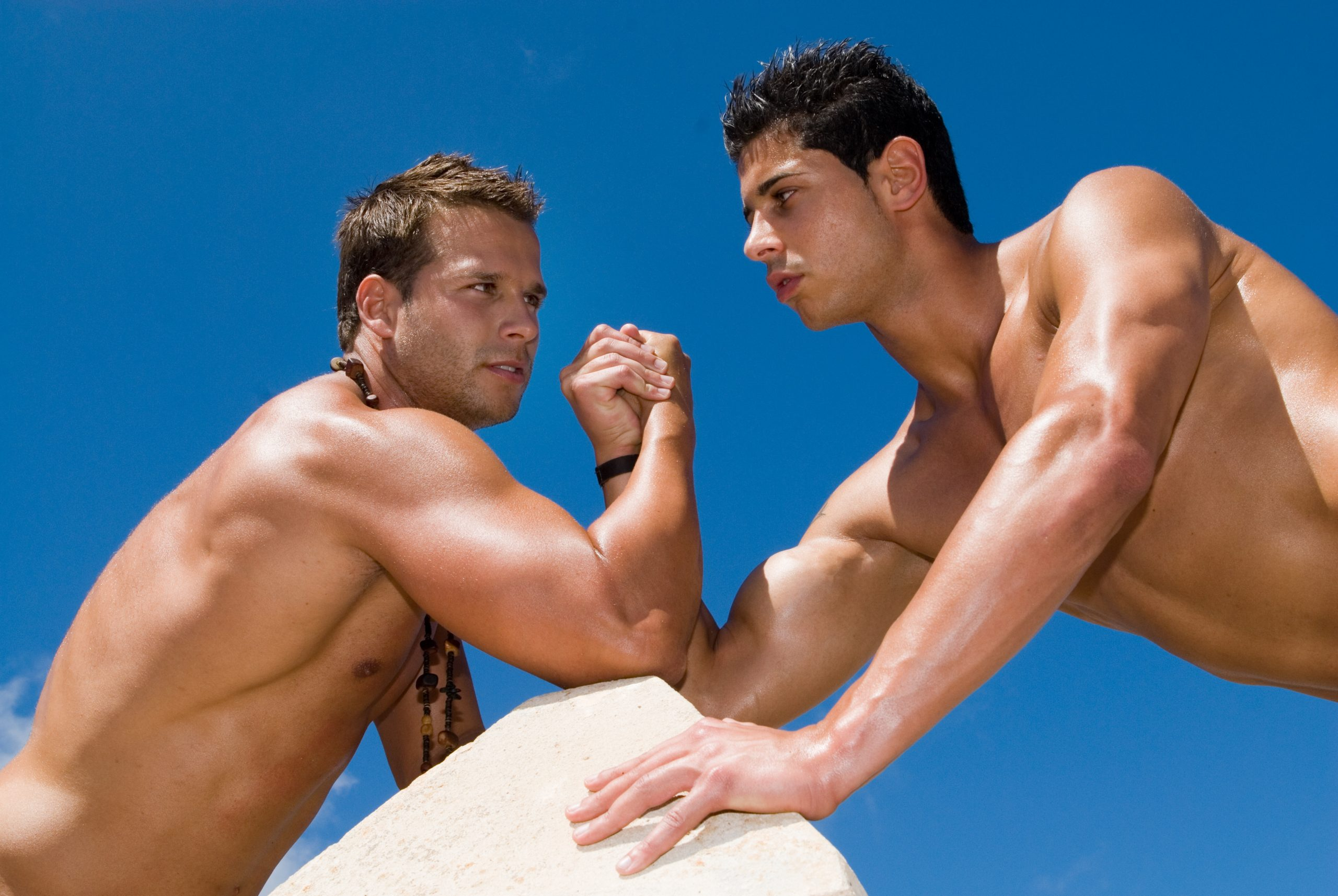Two gay shirtless men arm wrestle each other on a rock against a blue sky.