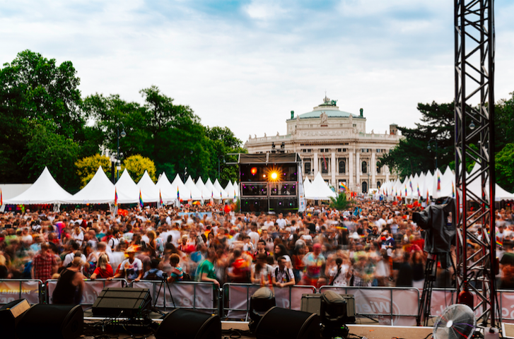 A music festival in Vienna, with white tents to the sides, a beautiful building in back, and a large crowd in the middle dancing in front of the stage with the DJ