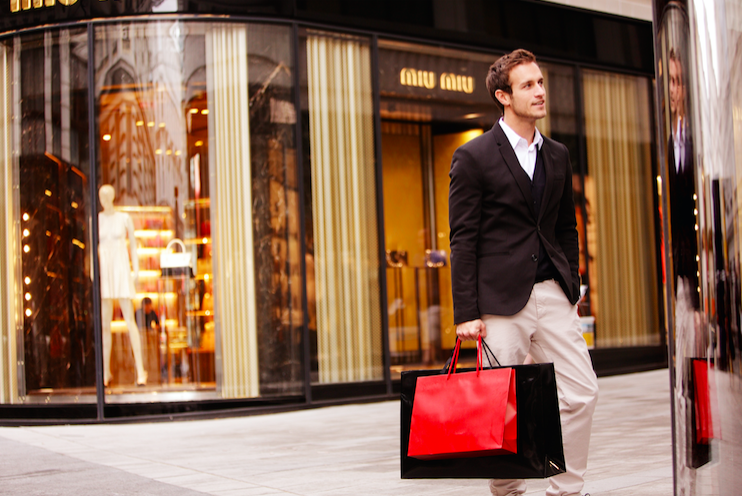 A gay man shopping in Vienna, with a mannequin behind him, while he's holding red and black shopping bags