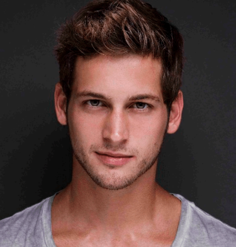 Max Emerson, an LA-based gay social media influencer, poses for the camera in front of a black background.