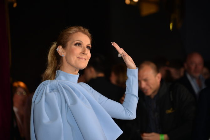 Celine Dion waves at the cameras at the premiere of