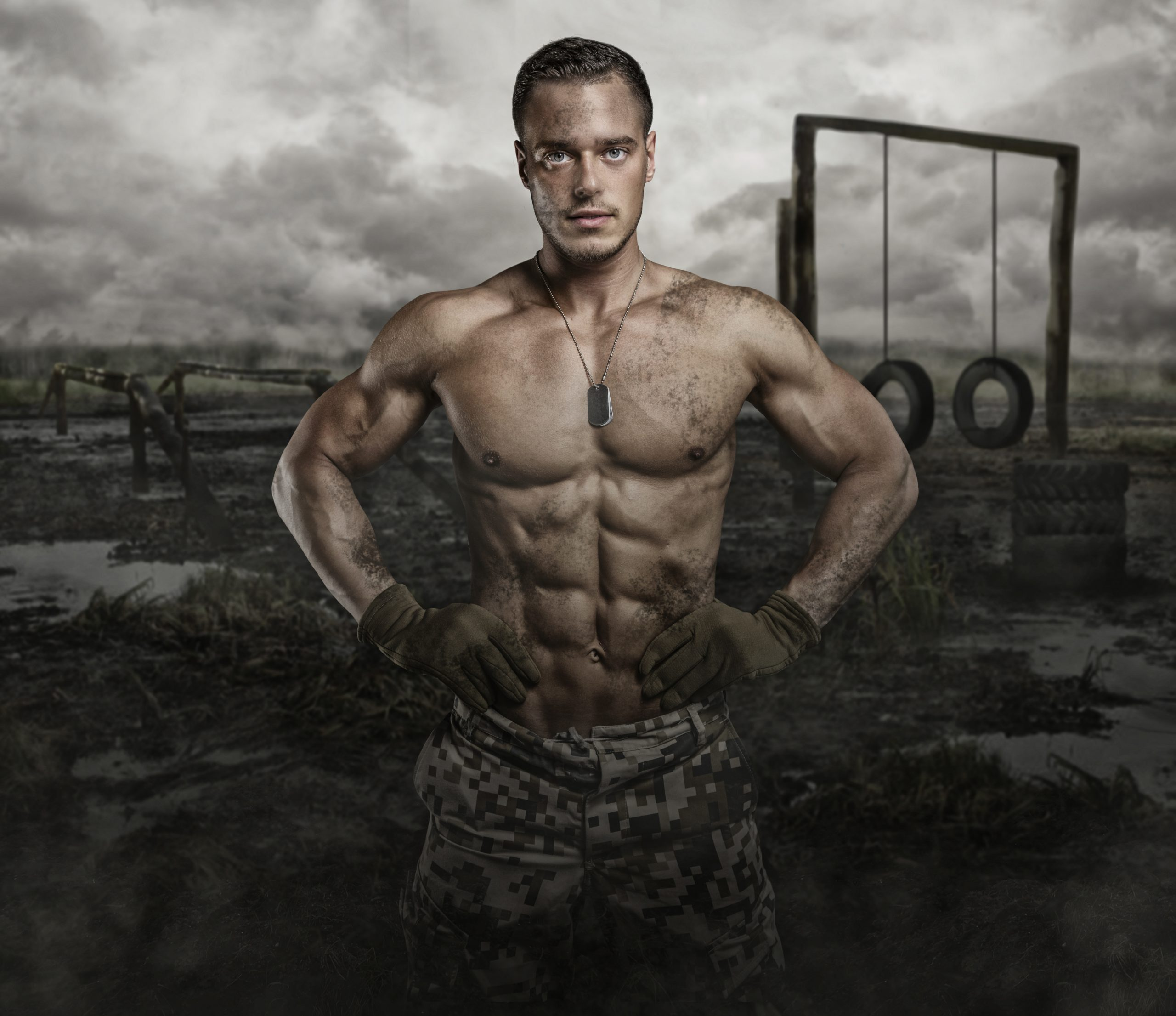 A United States marine poses shirtless, with defined abs and muscles, in front of a marine training course.