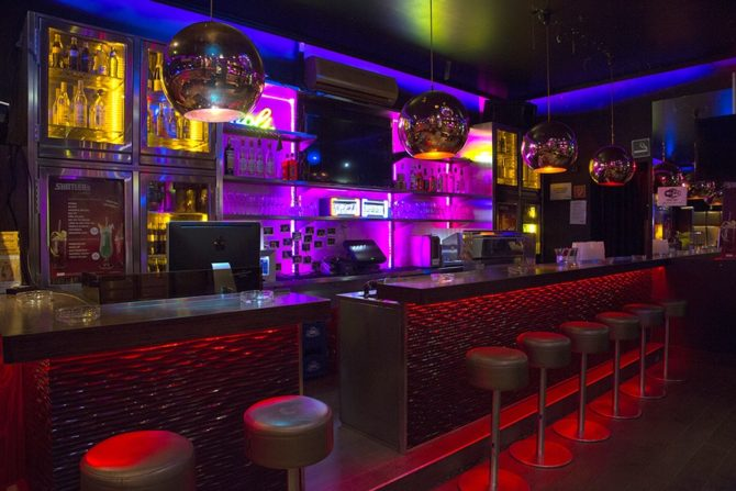 An empty Why Not club in Vienna, with purple bar lighting and red stool lighting. This is a queer bar in Vienna.