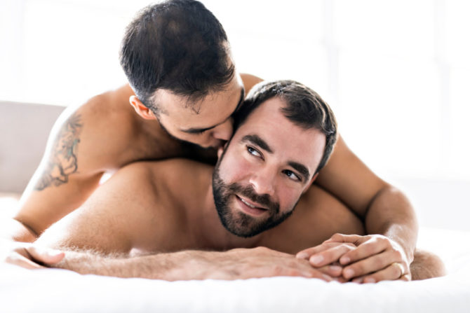 man on top of man kissing him in bed