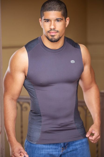 Anthony Bowens is a gay fitness influencer on Instagram, who poses here in a tight gym shirt.