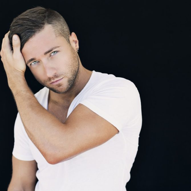 Colby Melvin is a fitness buff and underwear model, who is shot here posing in a white shirt in front of a black background.