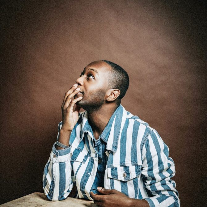 Jarvis Derrell is an Instagramer and Photographer, posing for the camera in front of a brown studio background.