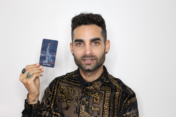 Brandon Alter holds up a tarot card