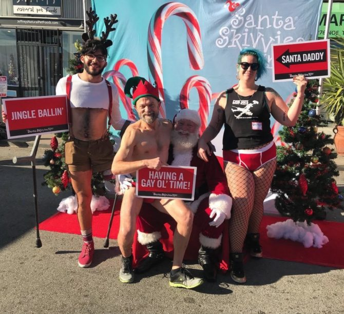 """Three Skivvies Runners are posing in a Santa's Wonderland scene with fake snow and pine trees. One of the runners is wearing an elf hat and sitting in Santa's Lap. The signs read """"Jingle Ballin'"""", """"Having a Gay Ol' Time!"""" and """"Santa Daddy."""