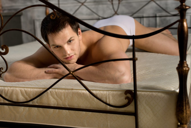 an alone in bed wearing white undies