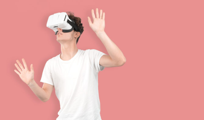 A young man wearing virtual reality goggles