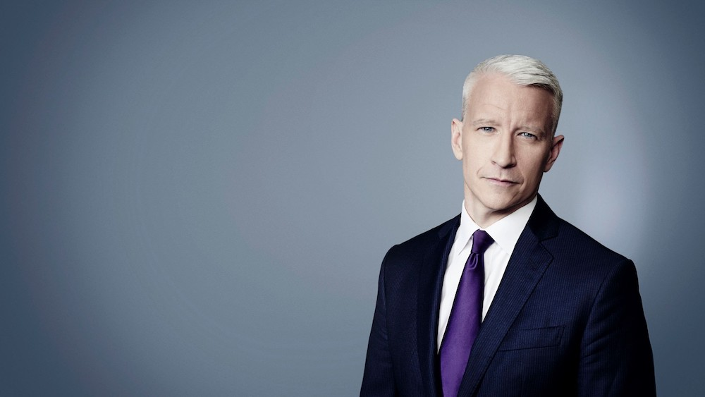 Anderson Cooper, the famous gay CNN anchor, poses against a black backdrop  with a