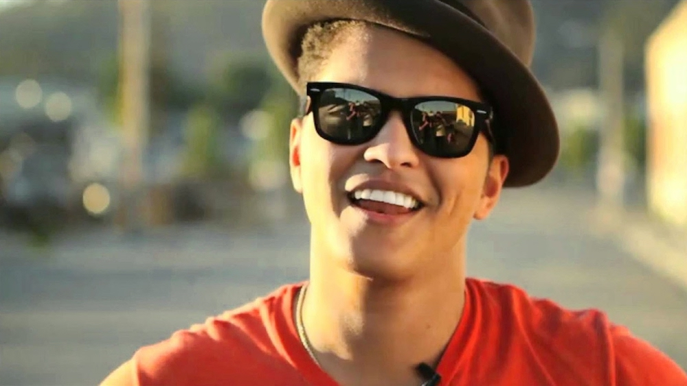 Bruno Mars smiles in a hat and orange shirt in California, alone.