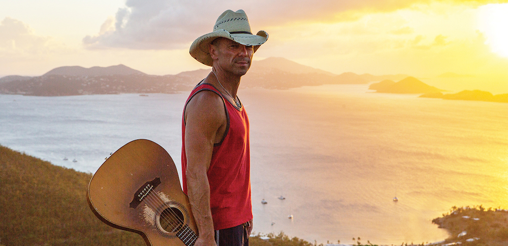 Kenny Chesney, a straight country singer, holds his guitar in front of a scenic sunset.
