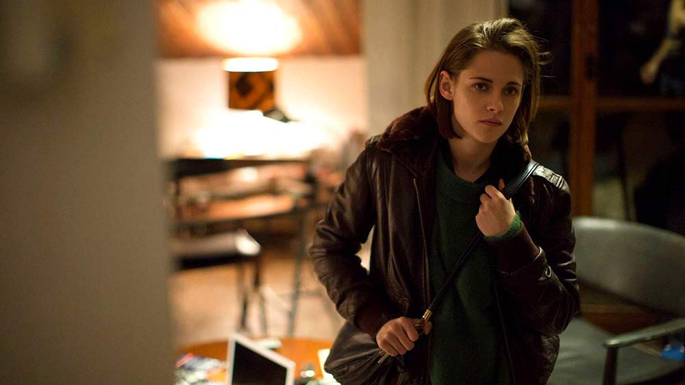 Kristen Stewart, who is gay, is dressed in a jacket while sitting in a living room.