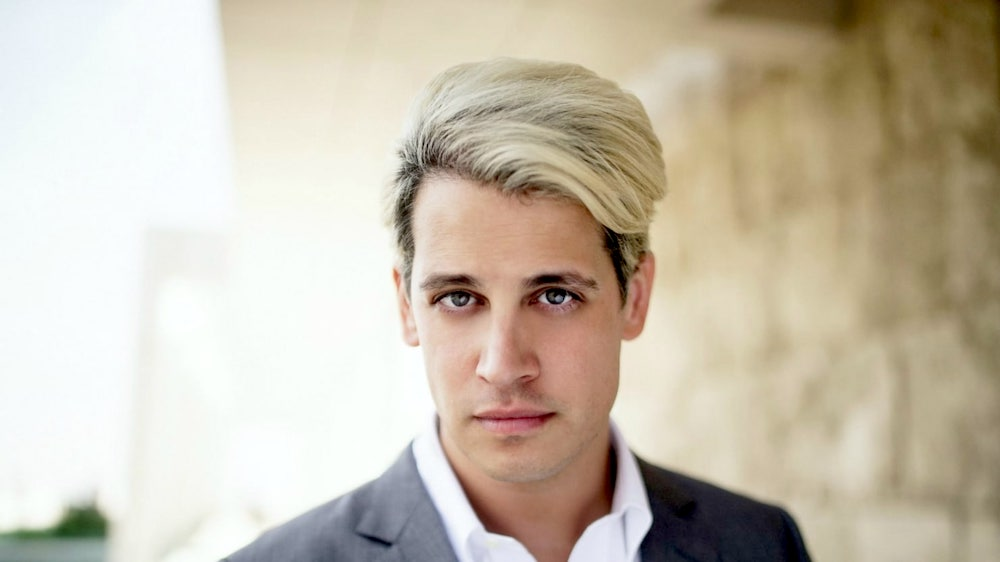 Milo Yiannopoulos gay, openly gay, poses against a scenic backdrop with  blonde highlights and