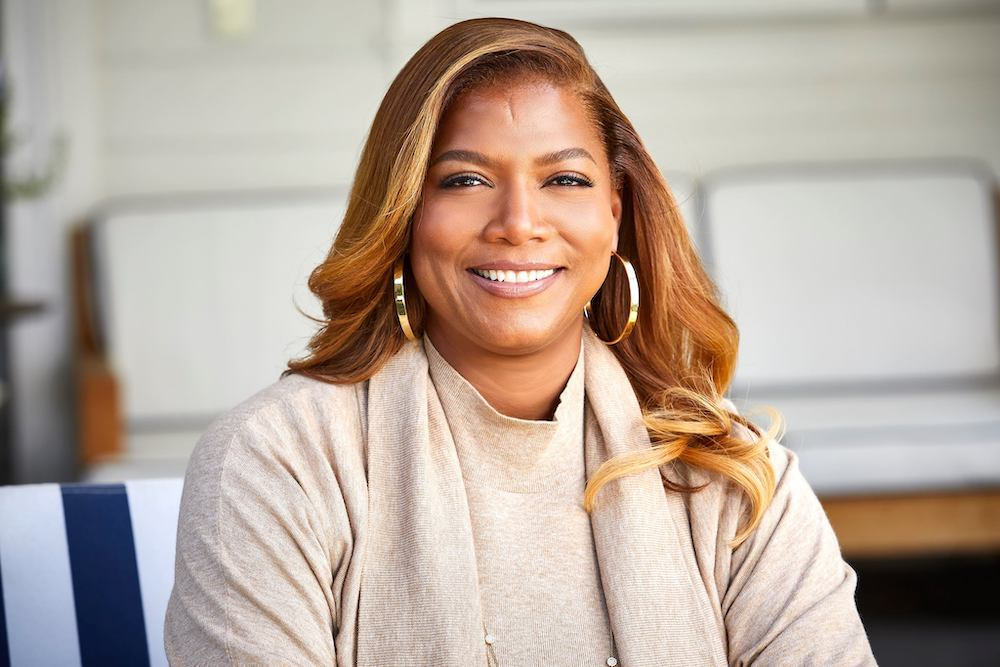 Queen Latifah, often presumed to be gay, poses for a headshot in a beige suit.