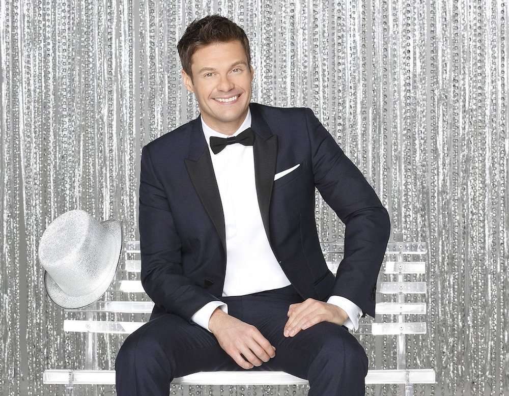 Ryan Seacrest poseses in front a silver sequin backdrop on a silver bench.