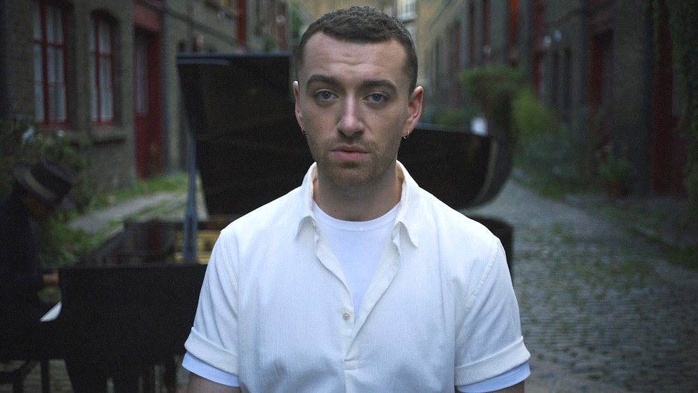 Sam Smith, who is gay, is wearing a white polo and standing in front of a black piano singing a love song.
