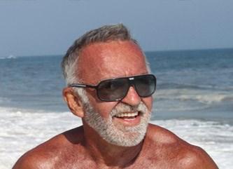 Photographer Tom Bianchi smiles on the beach