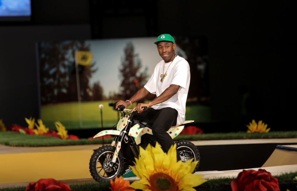 Tyler the Creator rides a small bicycle with flowers around him, inside, with a green hat and white shirt.
