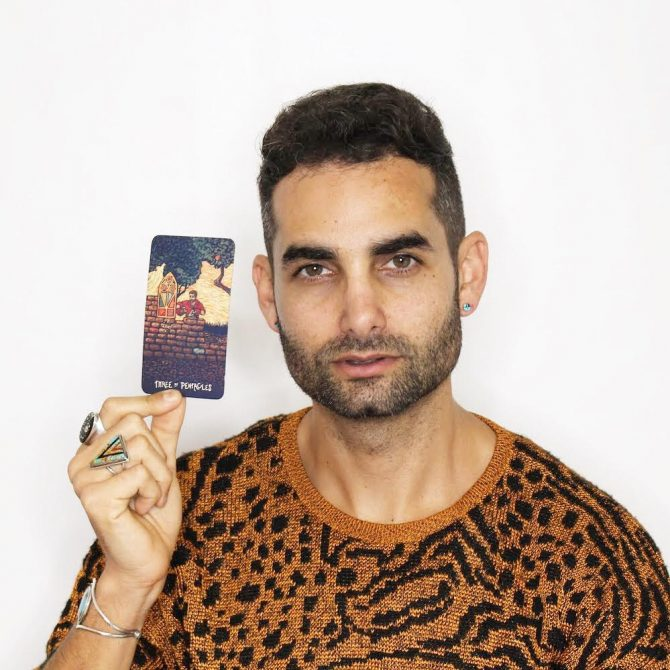 Brandon Alter holds up a tarot card