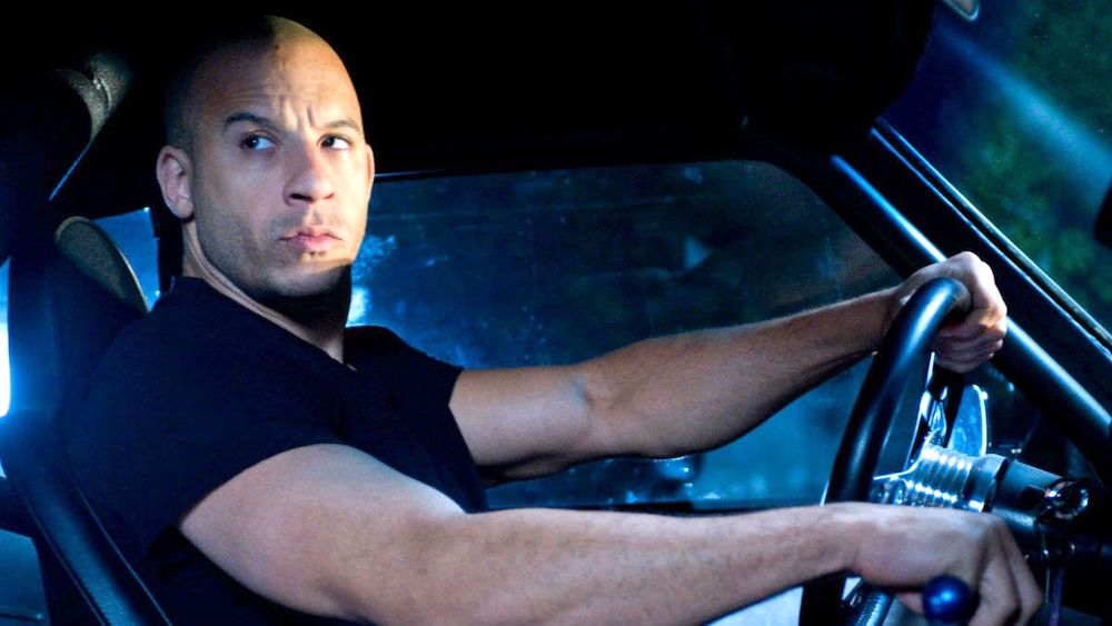 Vin Diesel in a blue-lit car on set for the Fast and the Furious