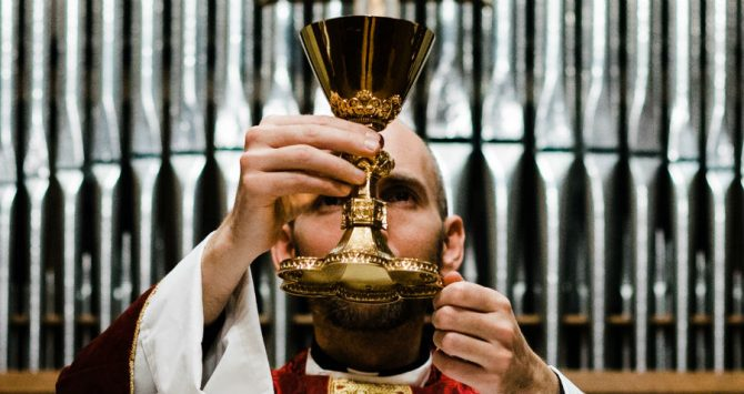 Priest holds a communion chalice