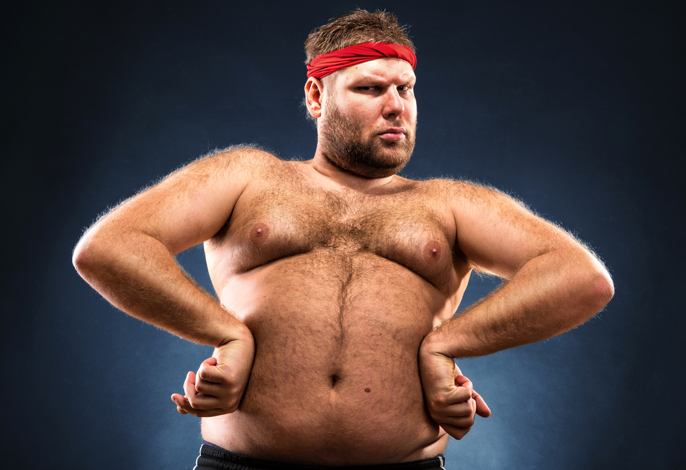 dad bod is a male body type or body shape that is a nice balance between working out and some who would enjoy eating eight slices of pizza. This photo features a man with a dad bod in front of a black background.