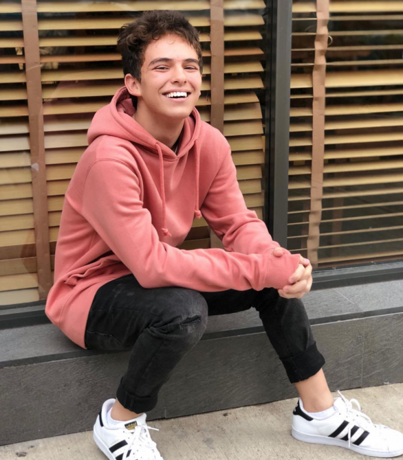 Joaquin Bondoni, Mexican Gay Actor, poses smiling on a sidewalk.