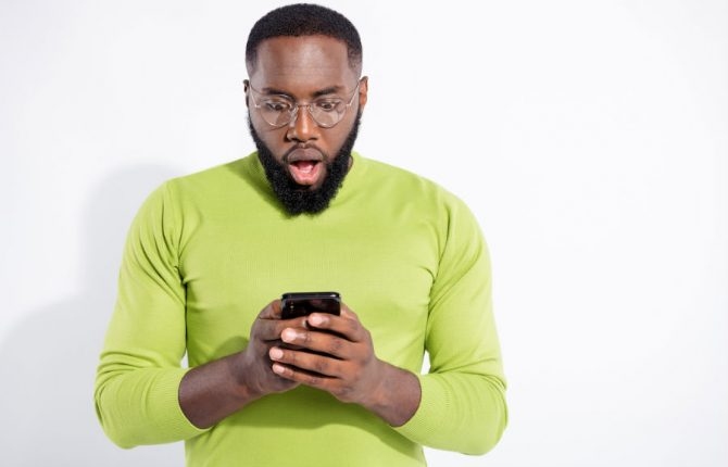 A surprised and shocked man looking at his cellphone