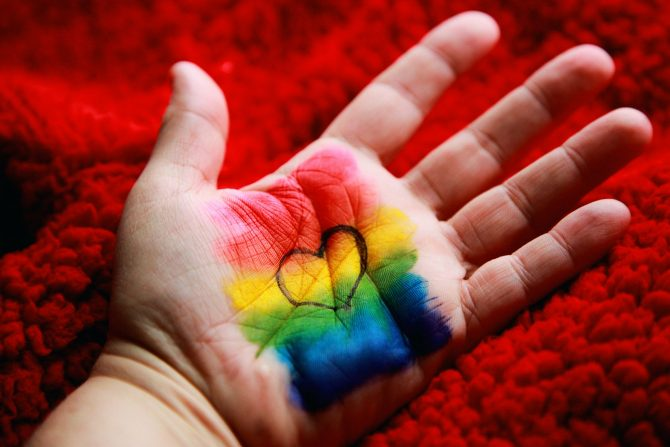A photo of a hand that is painted in rainbow paint with a heart in the middle.