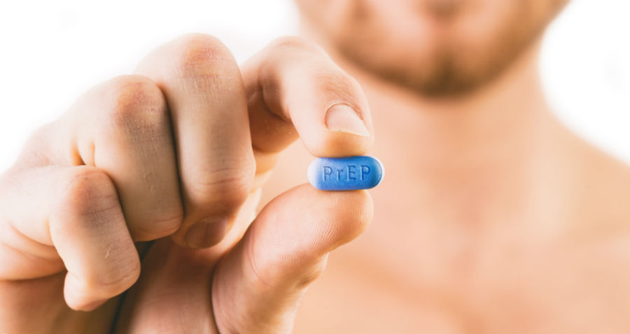 A man holds a PrEP Truvada tablet