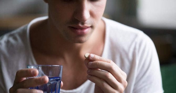 A man takes a medicine tablet