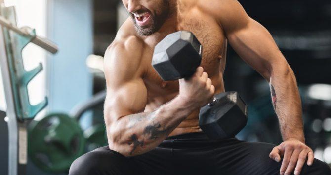 A bodybuilder flexes his biceps at a gym