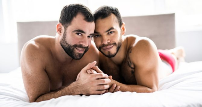 Two men in bed together, holding hands