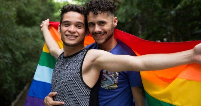 A gay couple hold a rainbow flag